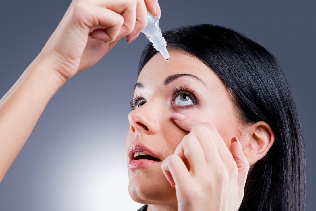 Mulher pingando colírio nos olhos secos