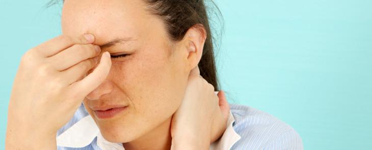 Mulher com dor de cabeça massageia a região dos olhos