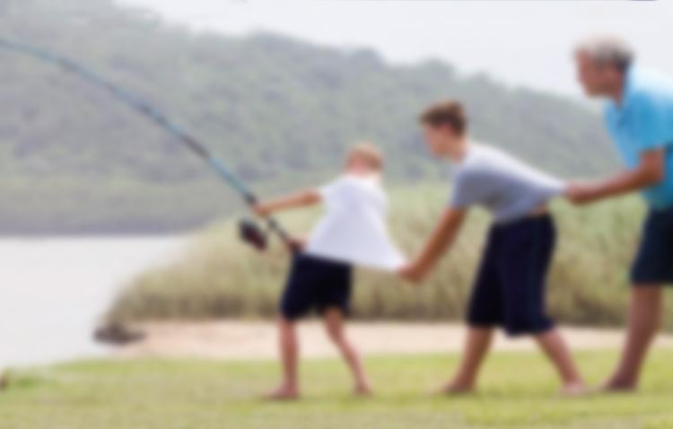 Pai e filhos pescam sob um ponto de vista fora de foco.