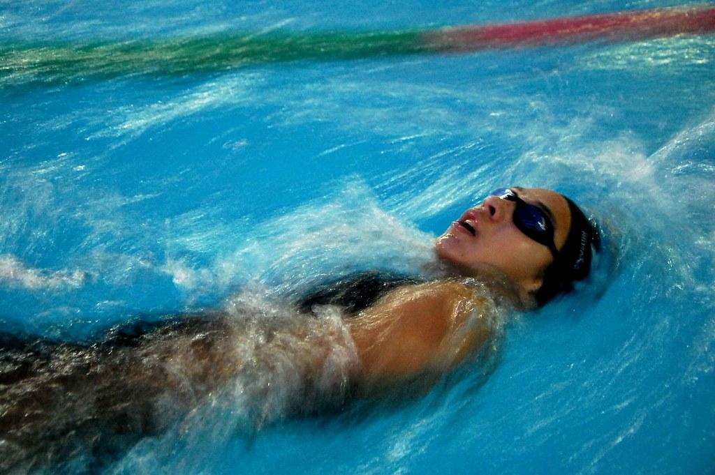 mulher nadando de costas em piscina