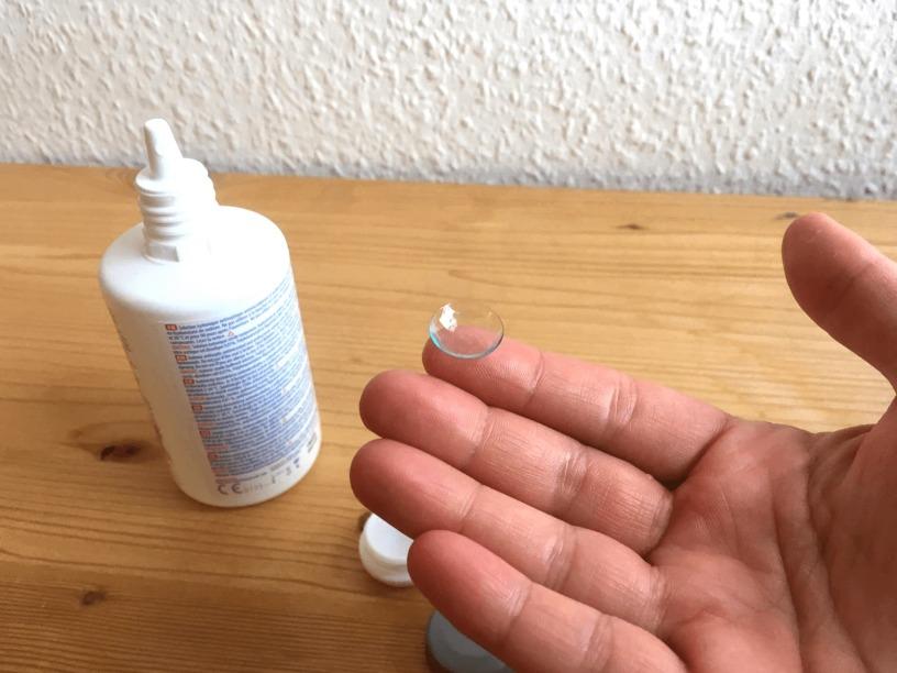 Mão masculina segurando uma lente de contato ao lado de uma solução de limpeza para a troca da lente de contato.