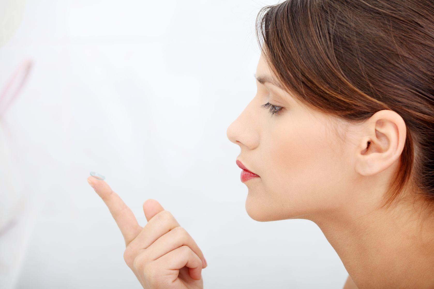 Mulher olhando para uma lentes de contato anuais sobre o dedo||Troca de lente de contato||