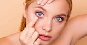 Mulher colocando as lentes de contato||close de olhos com lentes de contato||