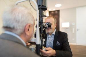 Homem fazendo um exame de vista  Mulher colocando as lentes de contato  Homem retira os óculos do rosto com semblante cansado.    
