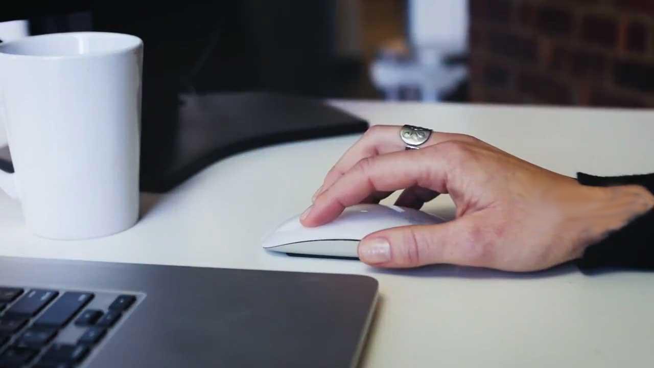 mão manuseia o mouse na frente de um notebook