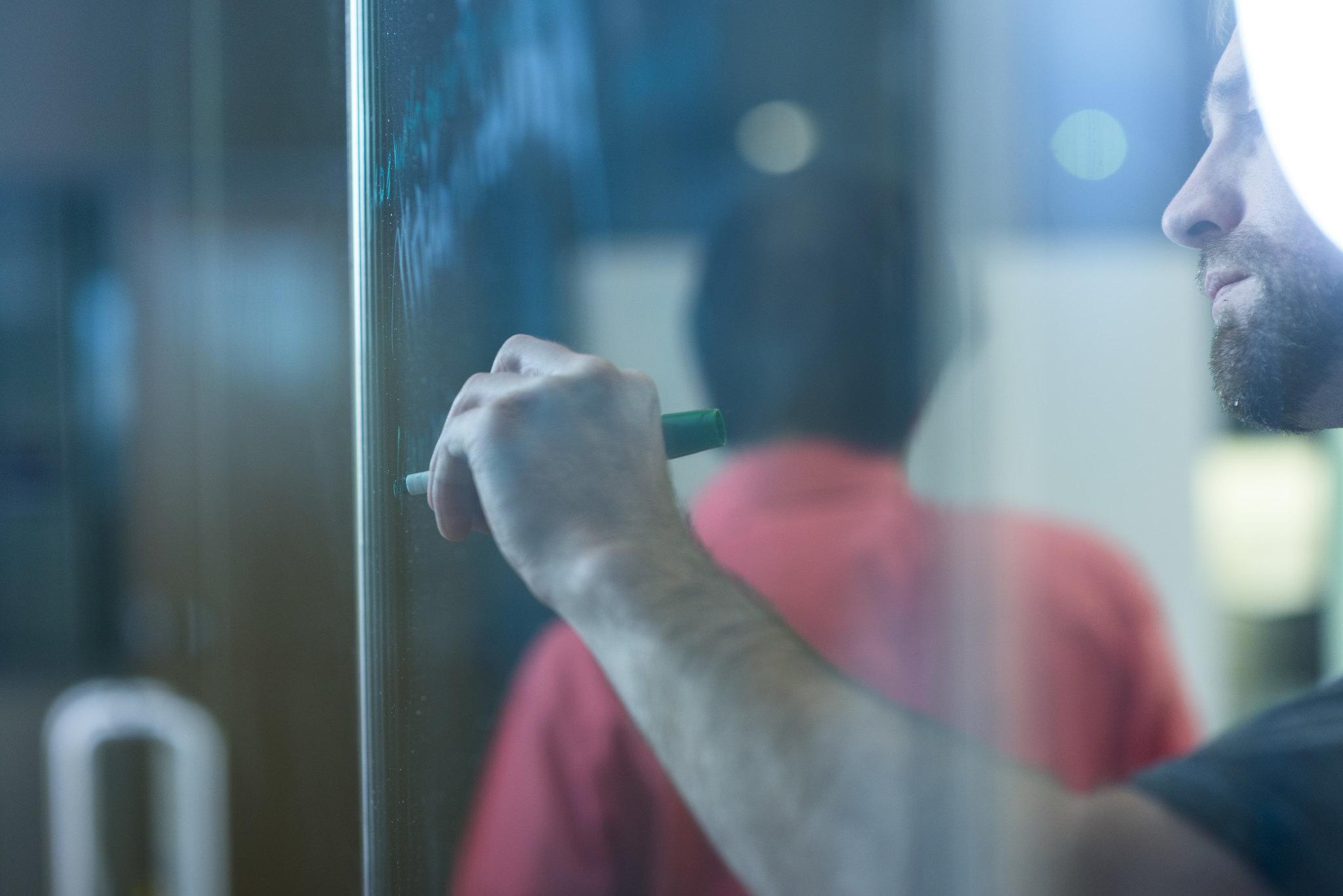 Homem escreve em lousa transparente