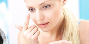 Mulher manuseia uma lente de contato que grudou em seus olhos