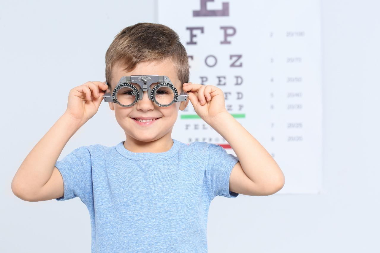 Garoto pequeno com equipamento oftalmológico em frente a uma carta de exame ocular