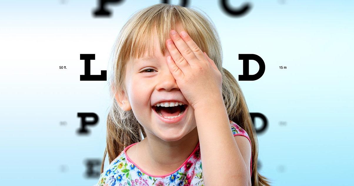 garota sorridente tampa um dos olhos em frente á carta de letras do oftalmologista