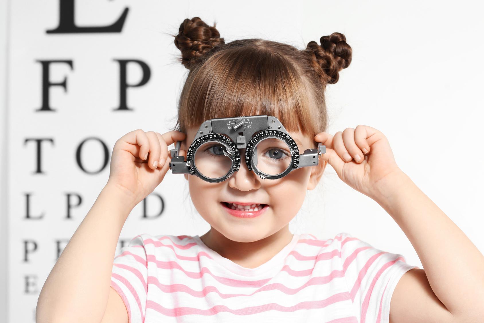 Menina faz brincadeiras com equipamento oftalmológico