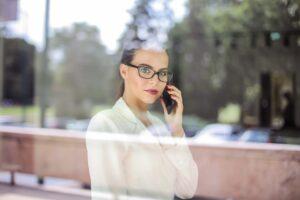 Mulher de óculos falando ao celular olhando pela janela  Mulher de óculos falando ao celular olhando pela janela