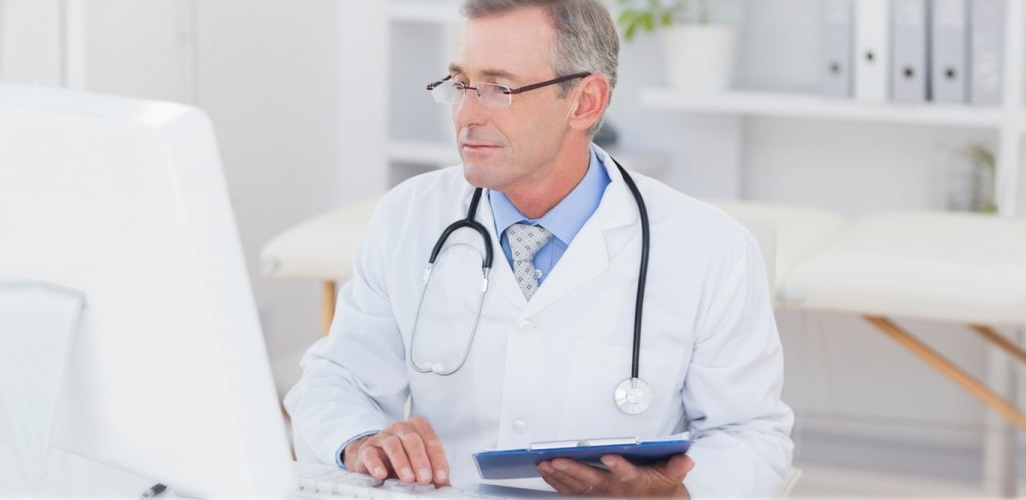 Médico olhando a tela de um computador. Ser organizado pode evitar uma entrega fora do prazo.