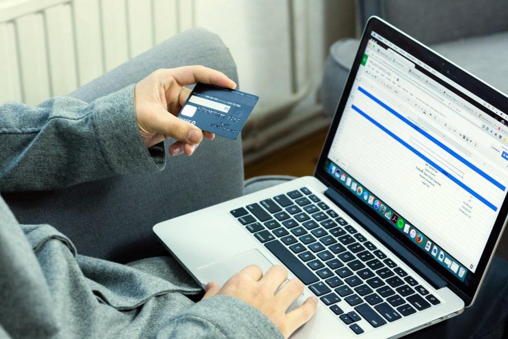 Mão de uma pessoa segura um cartão de crédito durante compra de lentes de contato online