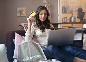 Mulher sorri confiante olhando a tele de um computador enquanto faz uma compra de lentes de contato online  Mulher sorri confiante olhando a tele de um computador enquanto faz uma compra de lentes de contato online