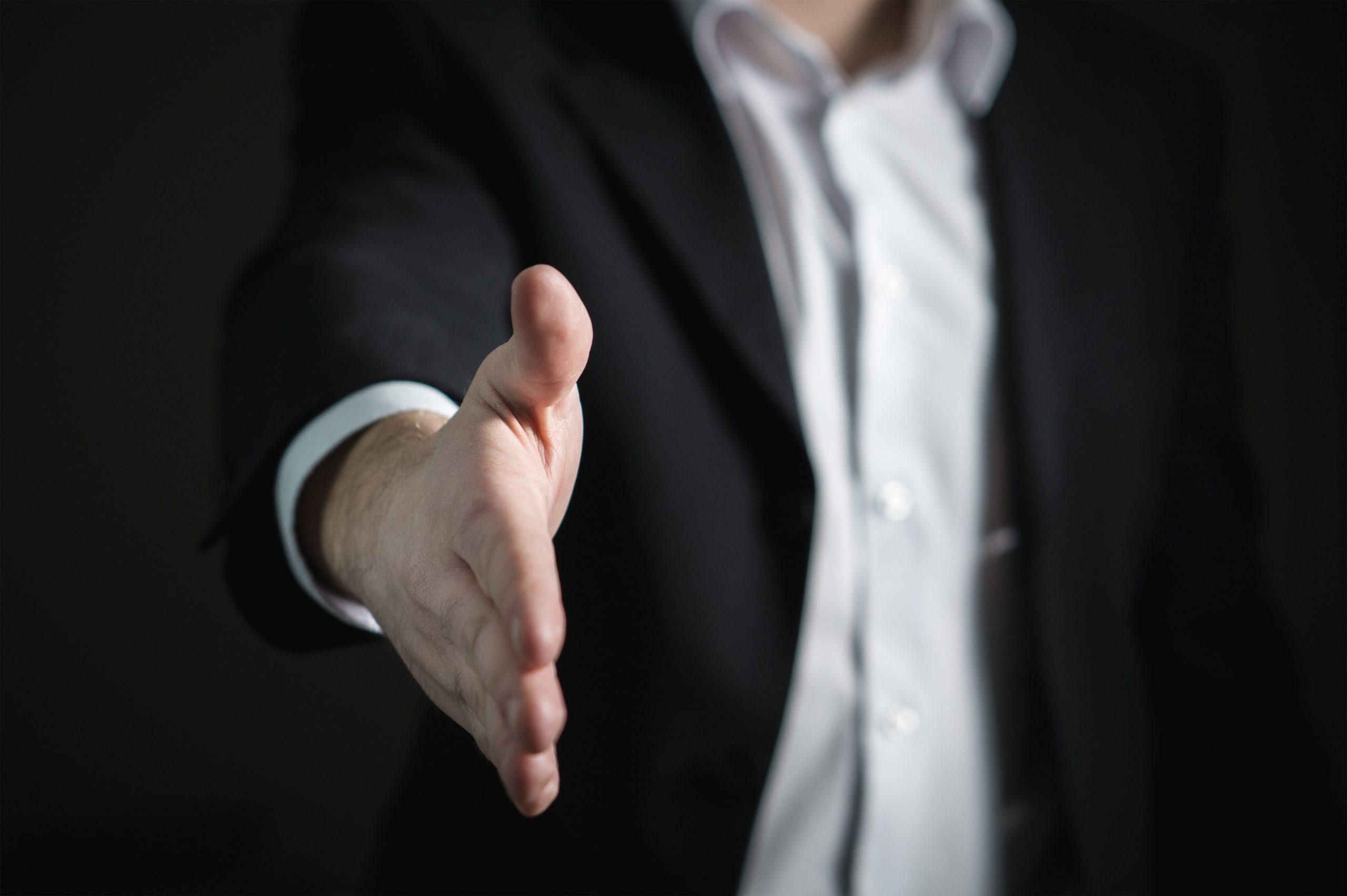 Homem estende a mão para concretizar a fidelização de fornecedores