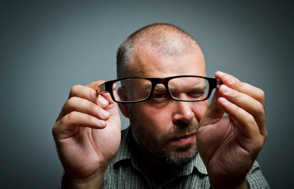 Homem analisa armação de óculos