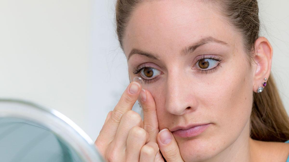 Mulher colocando a lente de contato no olho.