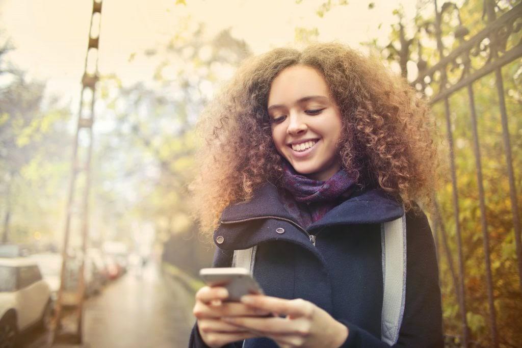 Mulher sorri digitando no celular