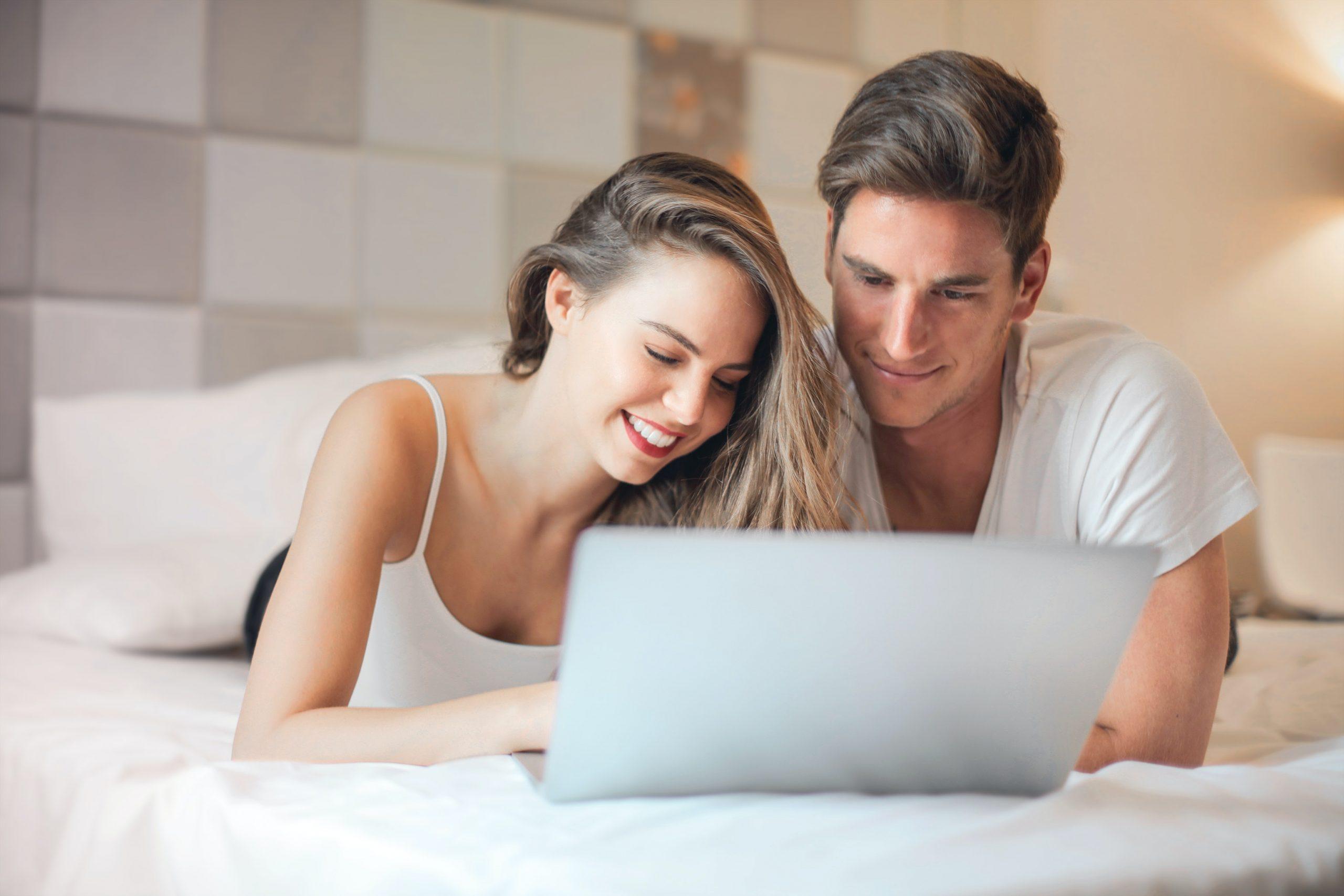 Casal compra lentes de contato deitado na cama através do ecommerce
