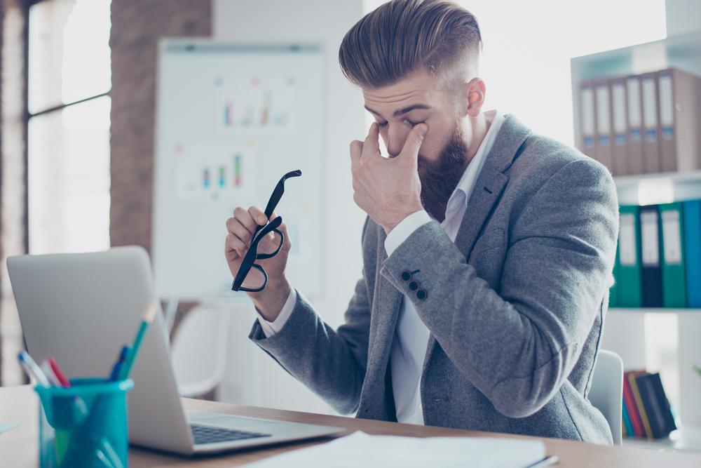 Homem retira os óculos do rosto com semblante cansado.